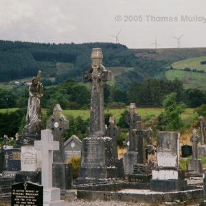 Church cemetery with windmill farm near Castlebar, Co. Mayo, Ireland.