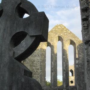 Celtic Cross and church wall at ruins of Cong Abbey, Co. Mayo, Ireland.